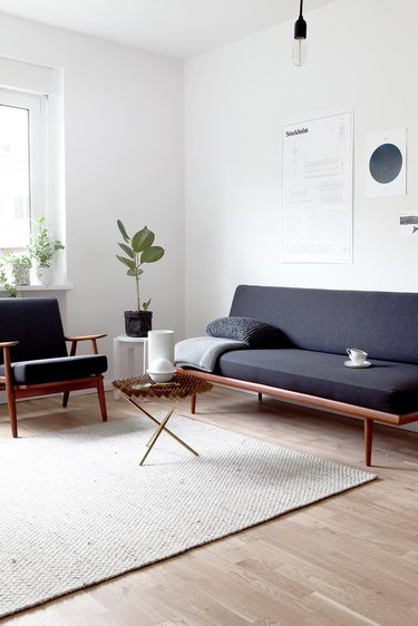 minimalist lighting in living room with dark gray futon and neutral rug