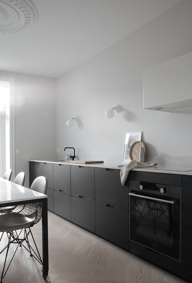 Scandinavian kitchen with black cabinets without hardware