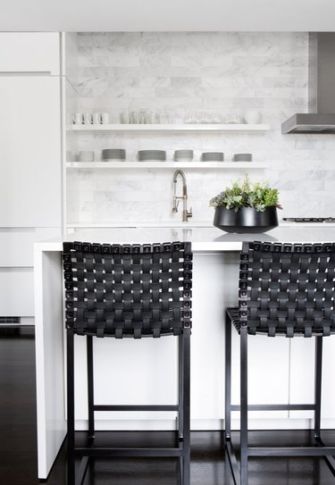 white kitchens with wood floors, black bar stools, and stainless steel hood