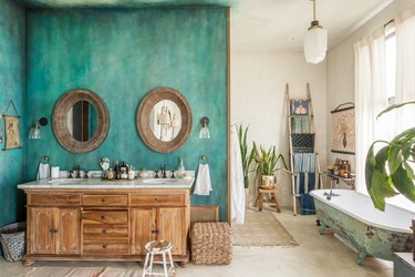 unique bathroom layout with wood sink vanity and white countertop, turquoise accent wall, and antique clawfoot tub