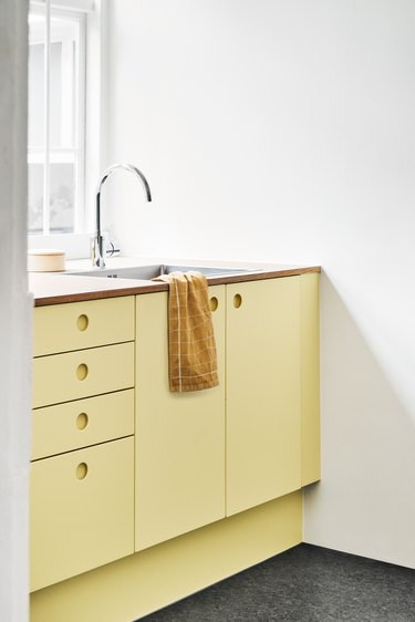 kitchen with yellow cabinets without hardware and wood countertop