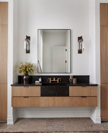 elegant bathroom lighting idea with black counter, corrugated drawers