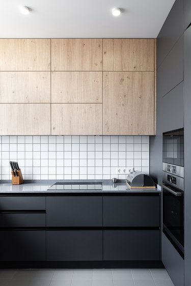 minimalist kitchen with black cabinets and light wood upper cabinets