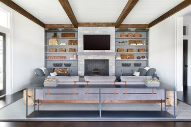 family room with fireplace and TV layout with built-in bookshelves and exposed wood beams