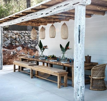 Rustic modern pergola with reclaimed wood beams and wood dining table and benches