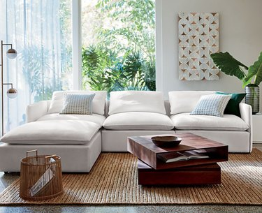 family room storage coffee table with white sectional couch and jute rug.