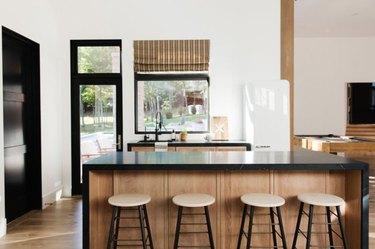 Waterfall kitchen island with black counter, light wood base.