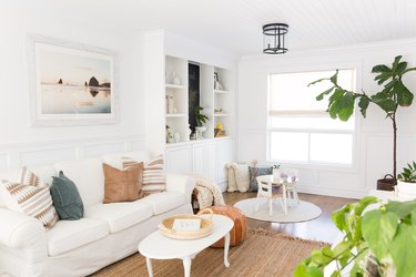 all white coastal family room with storage and jute rug