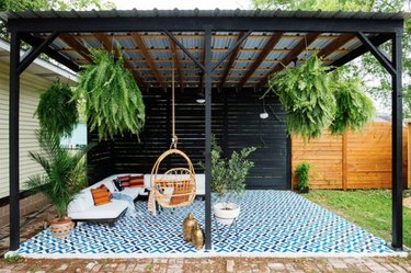 Black wood and metal modern pergola with sectional, hanging chair, plants and large outdoor rug.