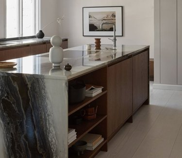 Waterfall kitchen island with gray marble, dark wood cabinets.
