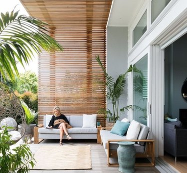 Modern pergola with two outdoor couches, rug, palms, woman seated.