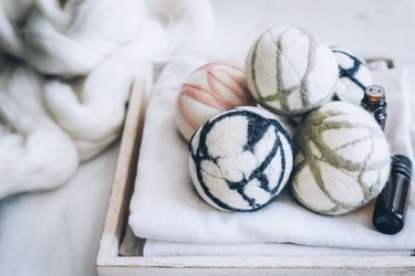 Wool felted dryer balls on tray with white cloth towels