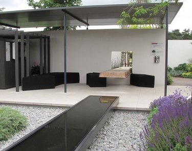 Covered modern pergola with metal roofing, black couch and chairs, modern fountain and native plants.