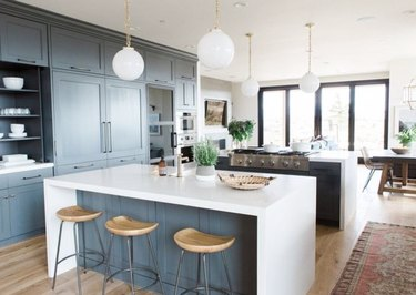 Two waterfall kitchen islands with white counters, gray cabinets, and white pendant lights.
