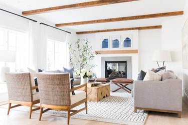 coastal living room with beige couch, wicker side chairs, tree trunk coffee table, wood beamed ceiling, fireplace, plant, white walls.
