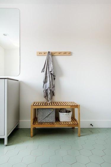 teak wood bench with minimalist bathroom storage and green hex tile