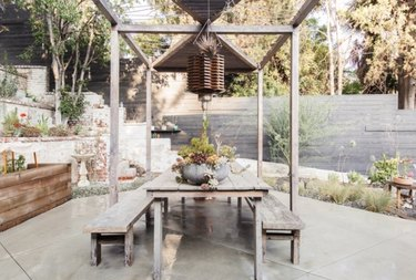 Outdoor dining set with modern pergola and concrete patio.