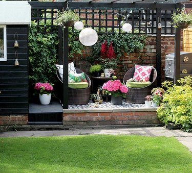 Black wood modern pergola with two wicker chairs, white Chinese lanterns and potted flowers.