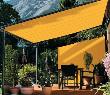 Yellow modern pergola with yellow fabric and black outdoor dining set and potted plants.
