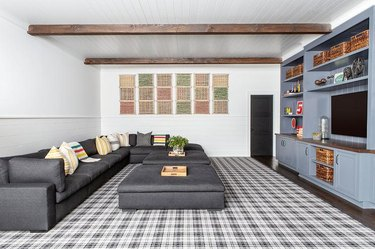 basement family room ideas with gray sectional and exposed wooden ceiling beams