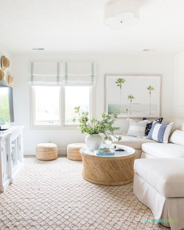 fresh coastal family room with rattan furniture and white roman shades