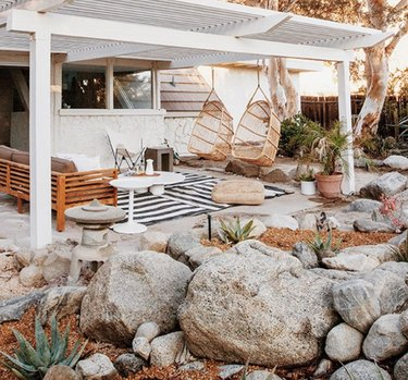 White wood modern pergola with hanging chairs, couch, outdoor rug and rock garden.