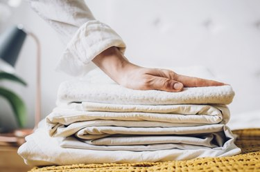 Folded bed sheets on top of mustard yellow blanket.