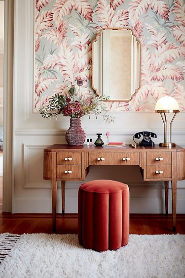 art deco colors with blush and brass with patterned wallpaper and wood desk