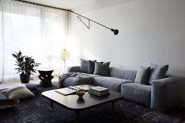 masculine boho decor in white living room with gray furniture