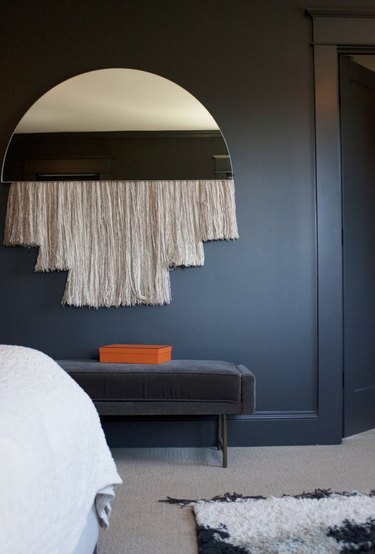 masculine boho decor with blue walls and half moon mirror