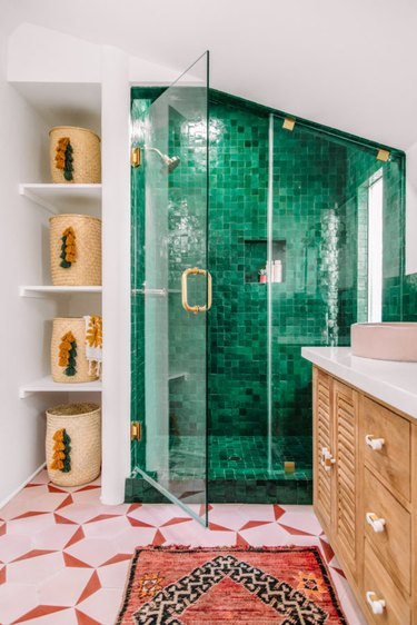 Green boho room with green tile shower and pink floor tiles