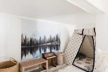 Kids' room with teepee, large canvas of outdoor scene, and toy piano.