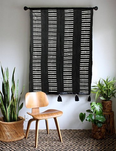 masculine boho decor with black and white wall hanging with wooden seat