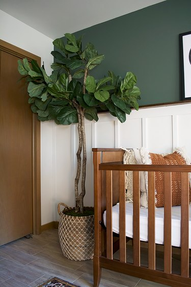 Green boho room with faux fiddle leaf fig tree and crib
