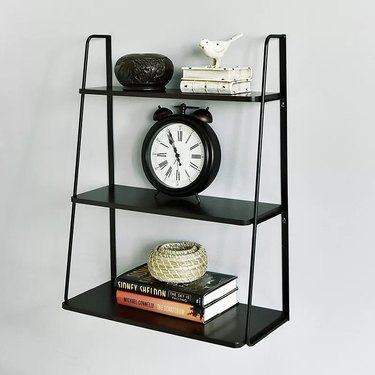 Black metal wall shelving unit with three shelves of varying sizes