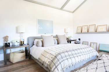 Small master bedroom idea with floating shelving and art above bed