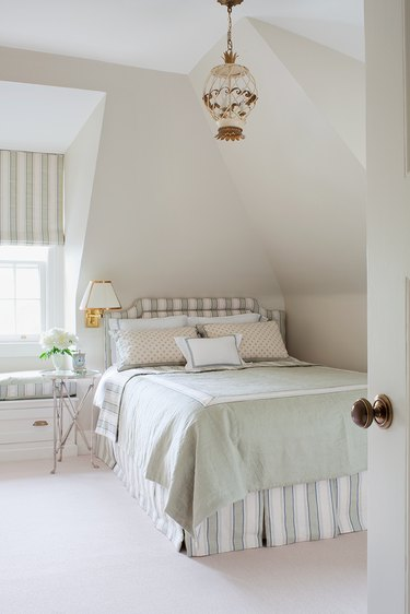 Small master bedroom idea with pendant light and bedskirt