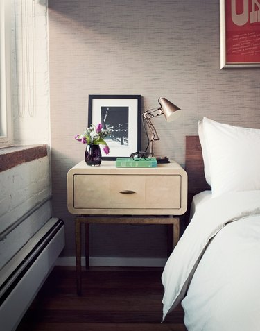 Small master bedroom idea with wallpaper and small nightstand