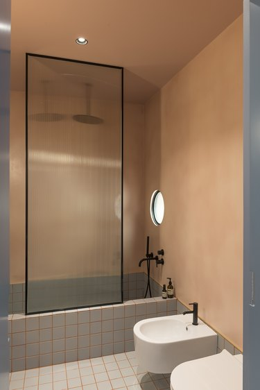 terra cotta minimalist bathroom with glass shower door and blue-gray tile tub and black shower fixtures