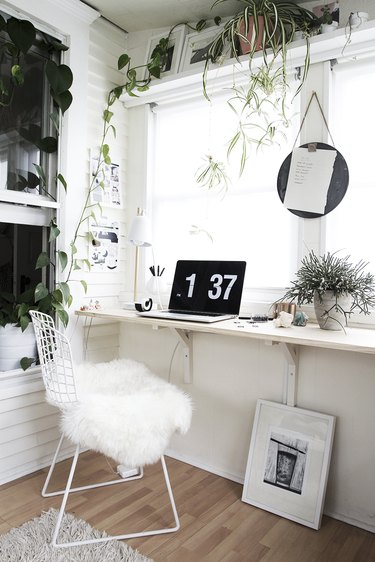 minimalist modern home office design with floating desk and plants