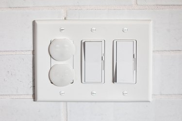 close up of electrical outlet and light switches