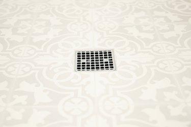 tan patterned shower floor tile, silver shower drain