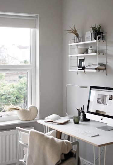 minimalist modern home office design with open shelving and gray walls