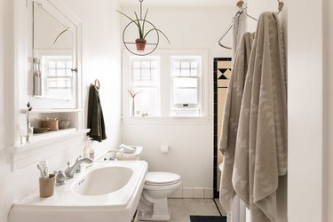white bathroom with pedestal sink, toilet and hanging towels