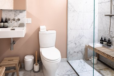 toilet with shower, shower bench wall-mounted sink and pink wall