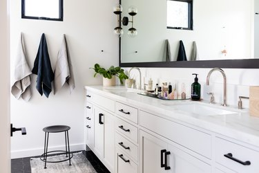 white bathroom vanity with black hardware, double sinks with silver faucet, three hanging towels, black stool, rectangular mirror with black trim