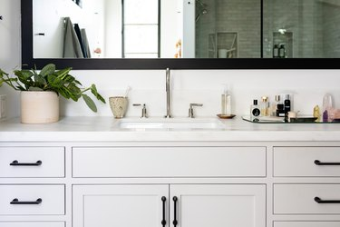 bathroom vanity with grey cabinets, single faucet sink and large mirror