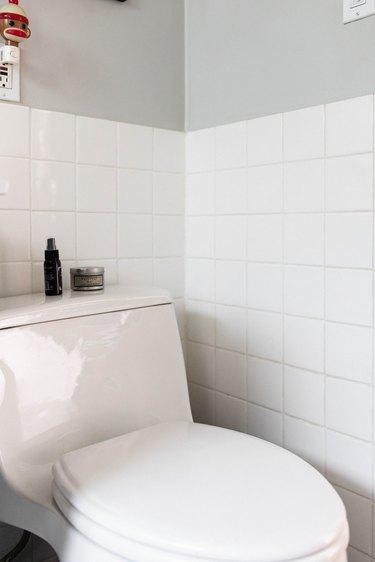 close up of toilet with tile backsplash