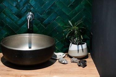 green herringbone wall tile, black vessel sink, wood countertop