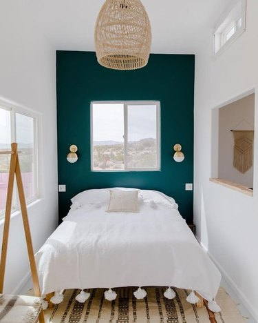 green boho room with woven pendant and tasseled duvet